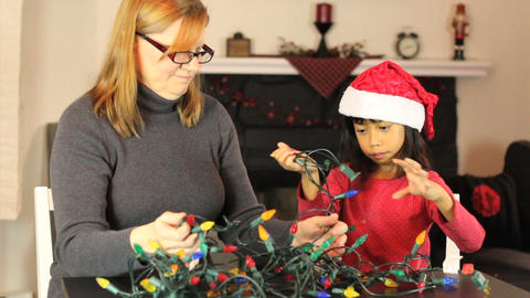 Mother And Daughter Untangling Christmas Lights Footage