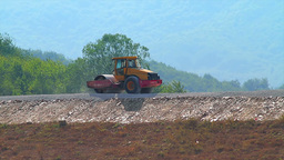 Compactor flattening road in rural area Stock Video Footage