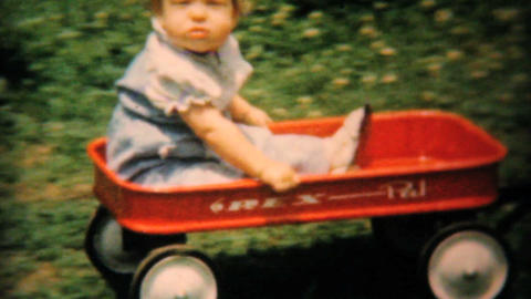 Baby Girl In Backyard Pulled In Red Wagon 1961 stock footage