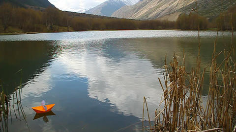 Orange paper boat floating in mountain lake Stock Video Footage