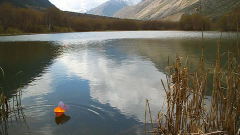 Orange paper boat floating in mountain lake Footage