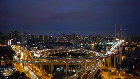 Aerial night heavy traffic on highway interchange,Brightly lit urban building Animation