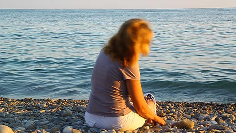 A woman sitting on the beach by the sea and throwi Stock Video Footage