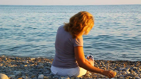 A woman sitting on the beach by the sea and throwi Footage