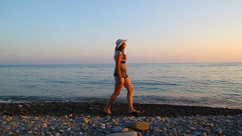Young beautiful girl in a hat walking on the beach Stock Video Footage