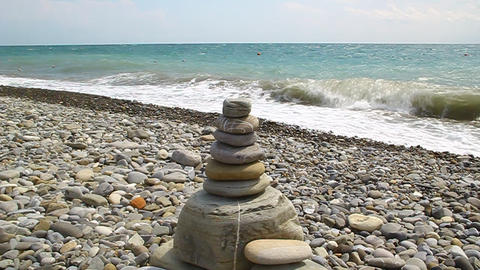 The pyramid of stones is on the beach Live Action