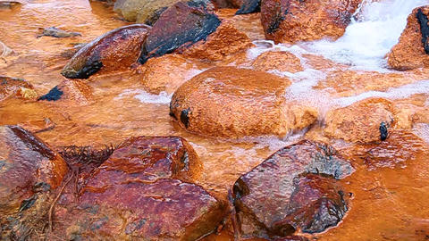Mineral water with iron flows over the rocks Stock Video Footage