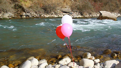 Three helium balloons are flown on the rocks by th Stock Video Footage
