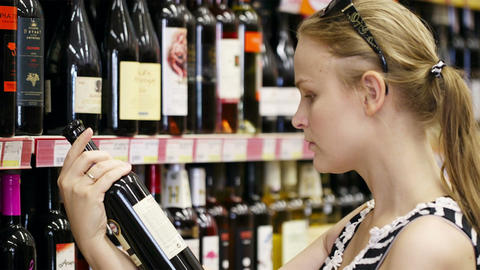 Woman shopping for alcohol in a bottle store Stock Video Footage