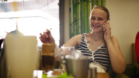 Woman in cafe speaking on the phone Stock Video Footage