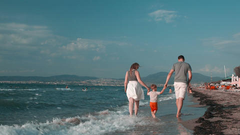 Happy family walking on the beach, in a summer day Stock Video Footage