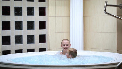 Mother enjoying a spa bath with her son Stock Video Footage