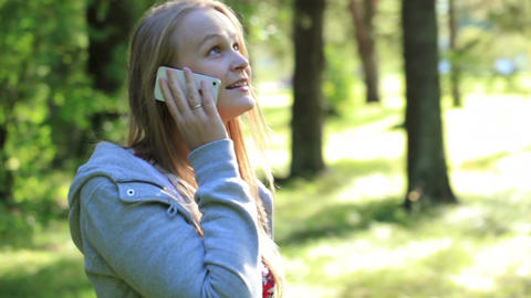 Woman chatting on her mobile phone outdoors Footage