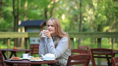 Young woman enjoying a pot of tea Stock Video Footage