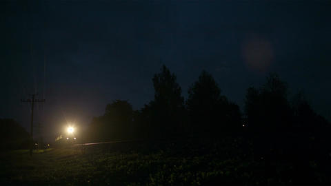 Train passing fast through a rural area, by night Stock Video Footage