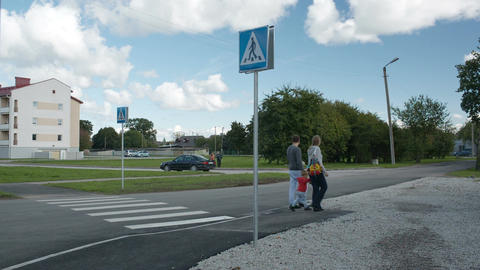 Family of three crossing the road Stock Video Footage