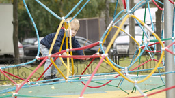 Happy little boy climbing on playground equipment Stock Video Footage