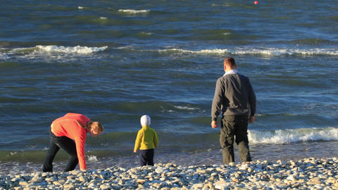 Family of three on pebble beach Stock Video Footage