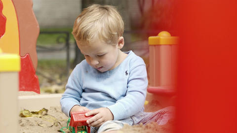 Boy playing with toy on playground Stock Video Footage