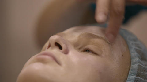 Cosmetitian creaming woman's face Stock Video Footage