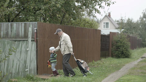Grandpa and grandson coming into gate Stock Video Footage