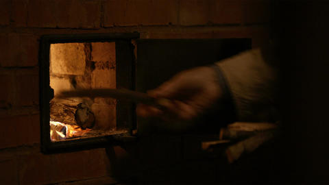 Putting firewood into the stove Stock Video Footage