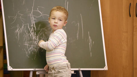 Creative little boy drawing on a chalkboard Footage