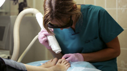 Doctor doing a laser treatment on a womans foot an Footage