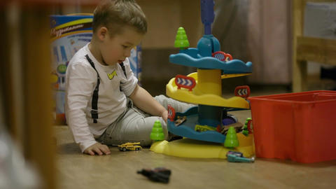 Little boy playing with a plastic parking garage Stock Video Footage