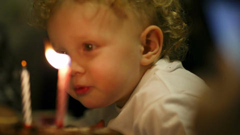 Little boy blowing out two candles on his birthday Footage