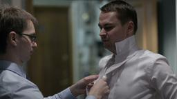 Groomsman tying groom's tie Stock Video Footage
