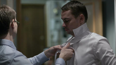 Groomsman tying groom's tie Footage