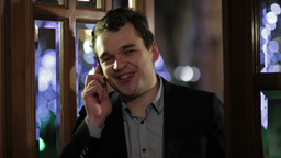 Man smiling happily as he chats on his mobile Stock Video Footage