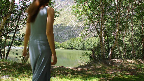 Young beautiful girl in a dress walks along the sh Stock Video Footage