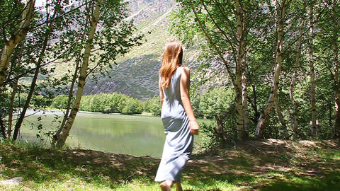 Young beautiful girl in a dress walks along the sh Footage