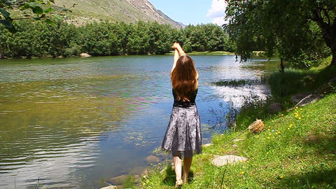 Young beautiful girl in a dress admires the mounta Stock Video Footage