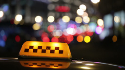 Illuminated taxi cab sign on a city street Stock Video Footage