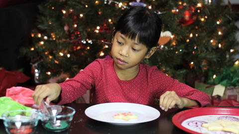 Asian Girl Adds Sprinkles To Christmas Cookie Stock Video Footage