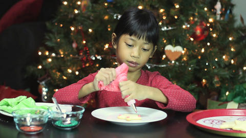 Asian Girl Decorating Christmas Cookie Footage