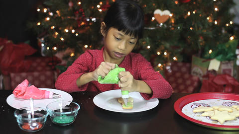 Girl Adds Green Icing To Snowman Christmas Cookie Footage