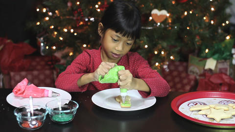 Girl Adds Green Icing To Snowman Christmas Cookie Stock Video Footage
