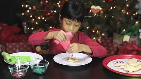 Girl Adds Red Icing To Christmas Cookie Stock Video Footage