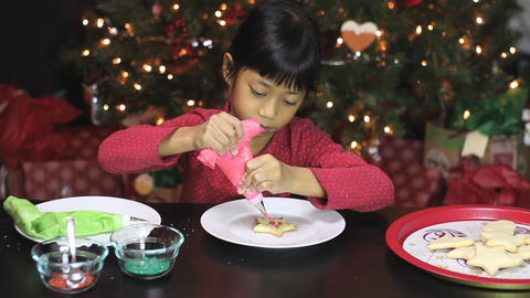 Girl Adds Red Icing To Christmas Cookie Footage