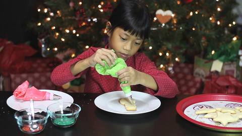 Girl Decorating Snowman Shaped Christmas Cookie Footage