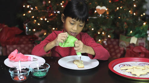 Girl Decorating Snowman Shaped Christmas Cookie Stock Video Footage