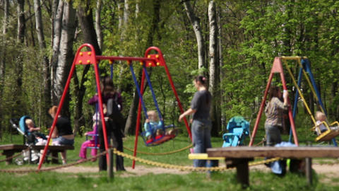 Children with their mothers, swinging in the park Stock Video Footage