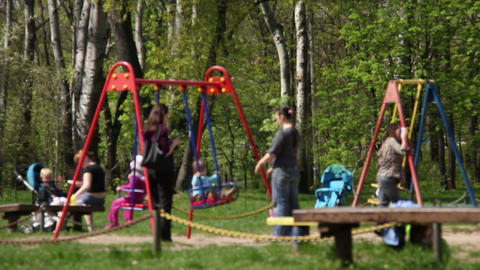 Children with their mothers, swinging in the park Footage