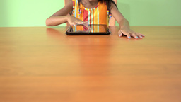 Table with Young Asian Girl Using a Tablet PC Stock Video Footage