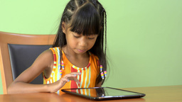 Young Asian Girl Playing With an iPad At The Table Stock Video Footage