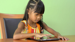 Young Asian Girl Playing With an iPad At The Table Footage